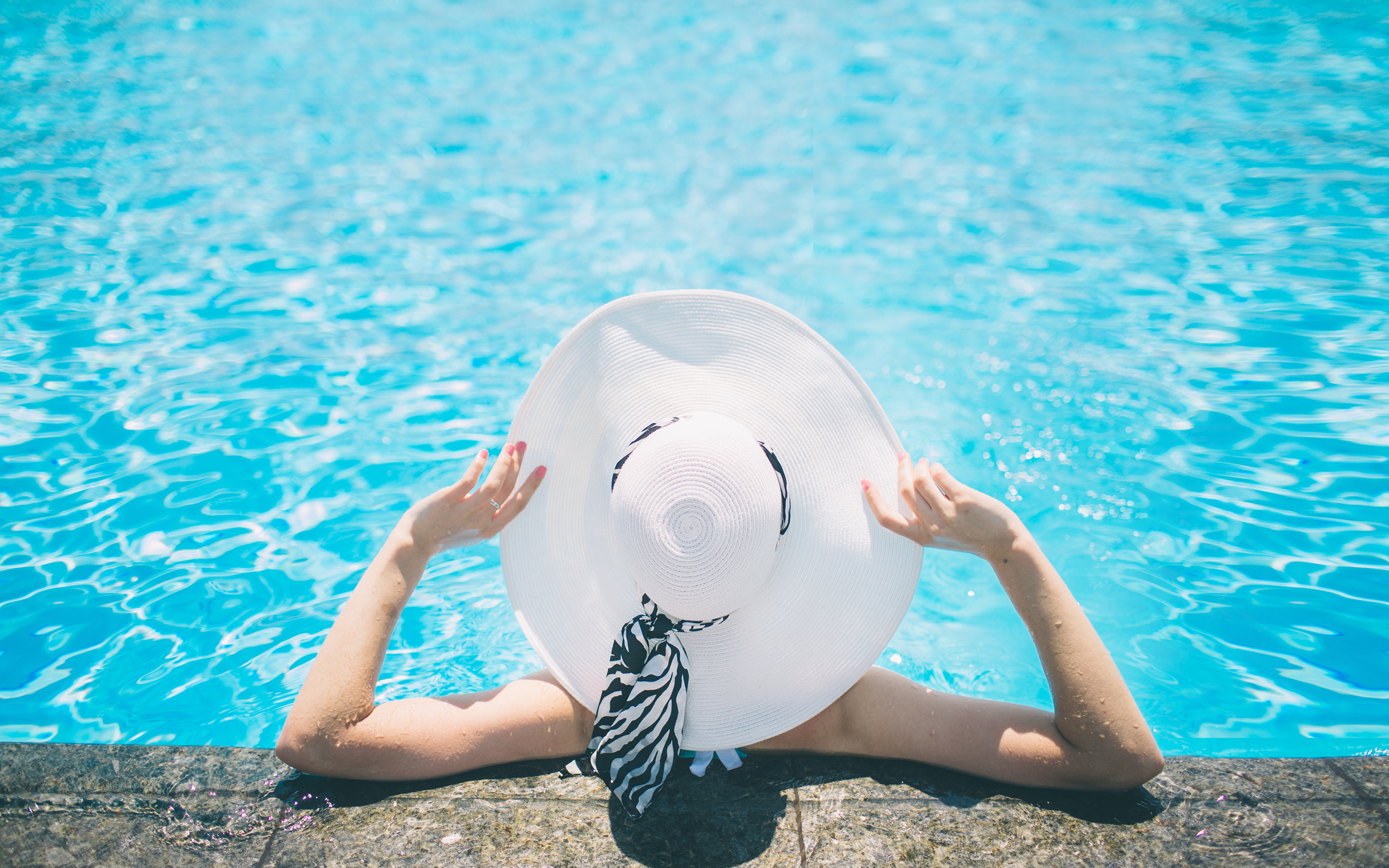 Woman lounging in the pool wearing a hat.